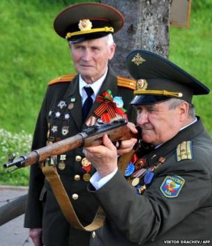 A Russian World War II veteran aims a Mosin rifle