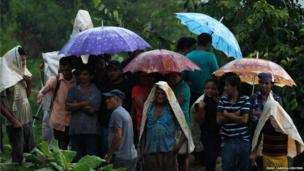 Miners and residents take cover from rain under umbrellas at the site of a landslide at a gold mine in San Juan Arriba