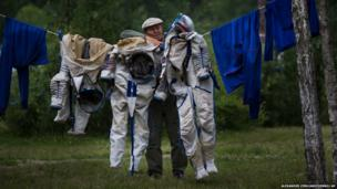 An employee at the Russian space training centre hangs out the space suits of cosmonaut Anatoly Ivanishin and flight engineers Kathleen Rubins and Takuya Onishi after a training session