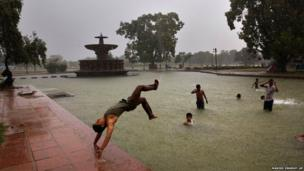 A boy somersaults into a water body as it rains in New Delhi, India