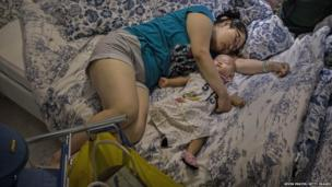 A Chinese shopper sleeps with her child on a bed in the showroom of the Ikea shop in Beijing, China