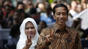 Indonesian presidential candidate Joko Widodo and his wife Iriana pose for pictures after casting their vote in Jakarta on 9 July, 2014