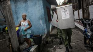 Election officers carry ballot boxes through slum area for distribution to the polling stations during preparations for the presidential election on 8 July, 2014 in Yogyakarta, Indonesia
