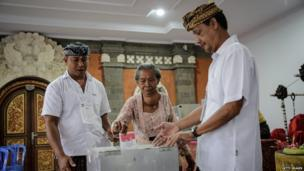 Election officers help a woman to cast her ballot during the Indonesia presidential election on 9 July, 2014 in Denpasar, Indonesia