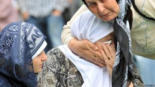 A Bosnian Muslim woman cries by the coffin of a relative at the memorial cemetery in the village of Potocari, near Srebrenica