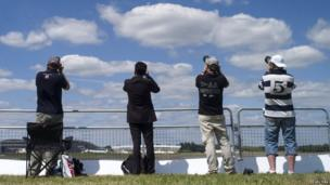 Four visitors to the Farnborough Airshow taking photographs