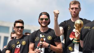 Mesut Oezil (L-R), Benedikt Hoewedes and Per Mertesacker from the German national football team hold the World Cup on the victory parade in Berlin