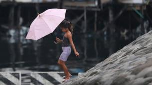 Girl with umbrella in Manila ahead of Typhoon Rammasun