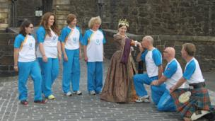 Woman in period costume is kissed on the hand by kneeling baton bearer