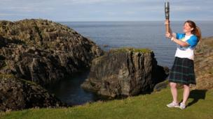 Kilted baton bearer poses at the edge of some sea cliffs