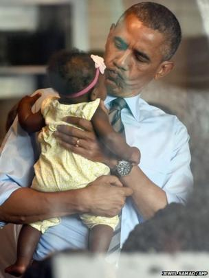 US President Barack Obama cradles a baby