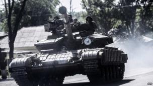 Pro-Russian militants sit on a tank in Donetsk, eastern Ukraine