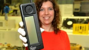 A museum employee holds up the IBM Simon, the first smartphone to go on sale 20 years ago