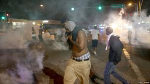 Demonstrators react as police fire tear gas at them while protesting the shooting death of Michael Brown in Ferguson, Missouri, 17 August 2014