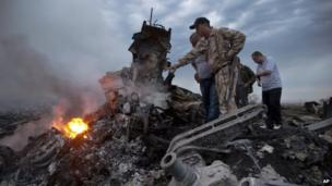 People inspect the crash site of a passenger plane near the village of Grabovo, Ukraine, on 17 July 2014.