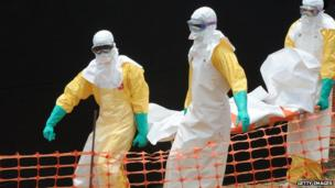 Staff of the 'Doctors without Borders' medical aid organisation carry the body of a person killed by viral haemorrhagic fever, at a centre for victims of the Ebola virus in Guekedou, on 1 April 2014.