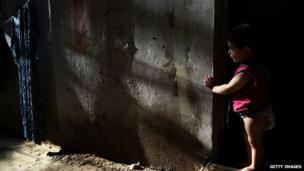 A Syrian child from the city of Daraa pauses in the doorway of her home in a poor neighbourhood with a high concentration of Syrian refugees on 1 July 2013 in Beirut, Lebanon