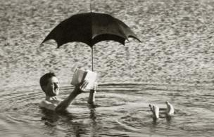 Man floating in Dead Sea while reading, under an umbrella