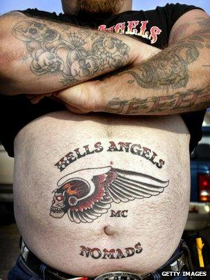 Nomad Dave shows off the new Hells Angels tattoo on his stomach as he attends a Hells Angels rally July 26, 2003 in Peru, Illinois