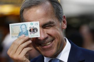 Bank of England Governor Mark Carney holding a new plastic £5 note up to his eye