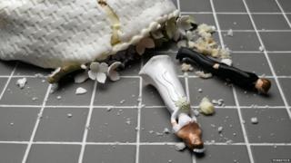 broken wedding cake on floor with figurines smashed