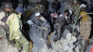 Syrian civil defence volunteers dig through the rubble of a mosque after an air strike on a mosque in al-Jineh in Aleppo province, 16 March 2017