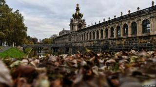 "The tower of the Crown Gate (Kronentor) of the baroque Zwinger Palace is reflected in the water of the palace moat filled with autumn leaves, in Dresden, Germany, 23 October 2017. Meteorologist predict the cloudy weather with temperatures around 11 degrees Celsius to continue in the next days in Germany""s Saxony state"