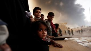 Newly displaced people wait to receive food supplies at a processing center for displaced people In Qayyara, south of Mosul, Iraq October 21, 2016