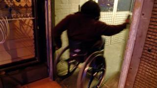 A man in a wheelchair going through a doorway
