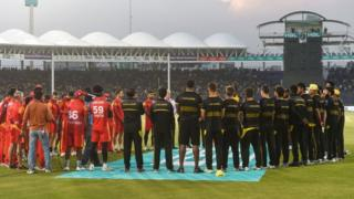 Cricket players stand in a circle for minute's silence