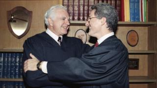 """In this Friday, Oct. 13, 1989, file photo, retired Judge Joseph A. Wapner of TV""""s """"The People""""s Court"""" congratulates his son, Judge Frederick N. Wapner, right, as he was enrobed as a Municipal Court judge in Los Angeles"""