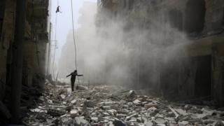 A man walks on the rubble of damaged buildings after an air strike on the rebel held Qaterji district of Aleppo, Syria (25 September 2016)