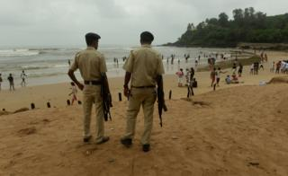 Indian policemen stand guard as they watch over tourists visiting Baga beach in Goa on September 24, 2016.