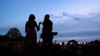 A silhouette at sunset shows Barack and Michelle Obama toast two champagne flutes before an assembled crowd, with the Washington Monument visible in the background