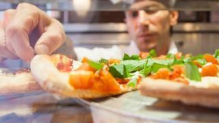 Un chef manipulando una pizza