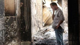 MSF employee inspects damaged clinic