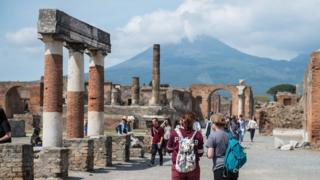 Tourists looking at the ruins of the forum at Pompeii.