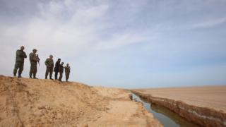 Soldiers overlook a trench, that forms part of a barrier along the frontier with Libya, in Sabkeht Alyun