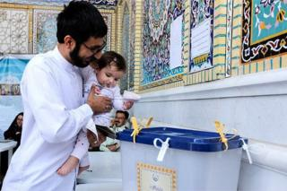 A man holding a little girl casts his vote in Shiraz, Iran, 29 April