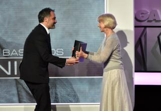 Miguel Sapochnik receives the award from Helen Mirren