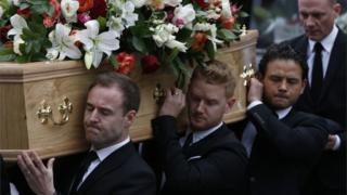 Cast members (left to right) Alan Halsall, Mikey North and Ryan Thomas carry the coffin of Coronation Street creator and writer Tony Warren