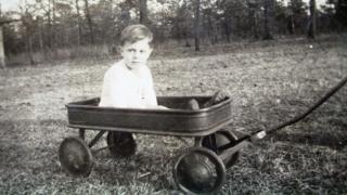 Donald Grey Triplett in a field, as a boy
