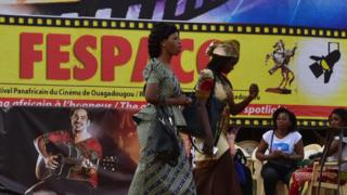 Festival-goers walk past an official poster of the Fespaco