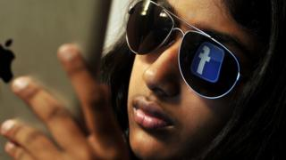 The 'Facebook' logo reflected in a young Indian woman's sunglasses