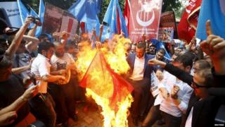 Demonstrators set fire to a Chinese flag
