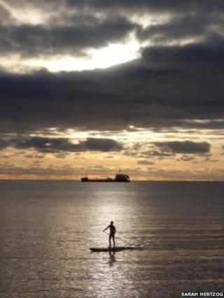 A figure on a paddle board in the sea is silhouetted in the sunrise
