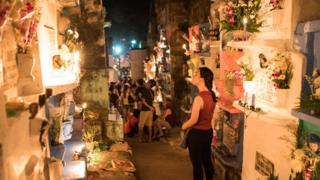 A woman stares at a group of colourful gravestones, behind her people are gathered at night in a well lit cemetery.