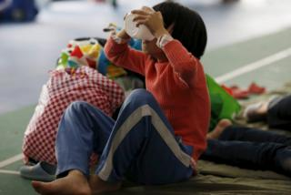 An evacuee girl eats food in a shelter set up at a gymnasium near the industrial park hit by a landslide in Shenzhen, Guangdong province, 22 December 2015