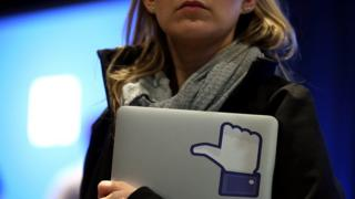 "woman holding laptop with Facebook ""thumbs up"""