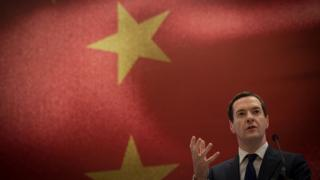 George Osborne makes a speech in front of a large Chinese flag